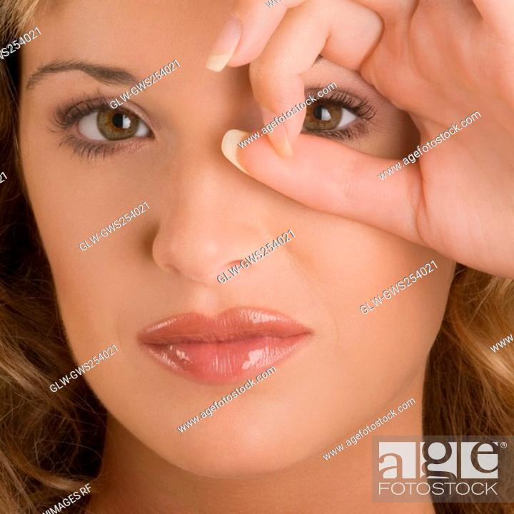 Stock Photo: Portrait of a young woman looking through a circle formed by her fingers.