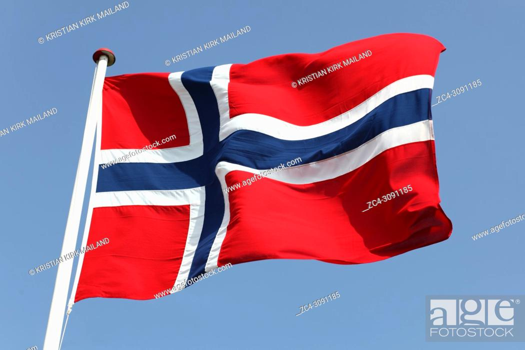 Stock Photo: Norway's Flag on flagpole against blue sky.