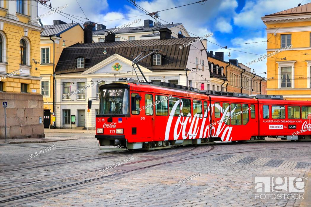 Stock Photo: Moving HSL tram with Coca-Cola advertising and Sederholm House, the oldest building in inner city, in the background. Helsinki, Finland. May 25, 2020.