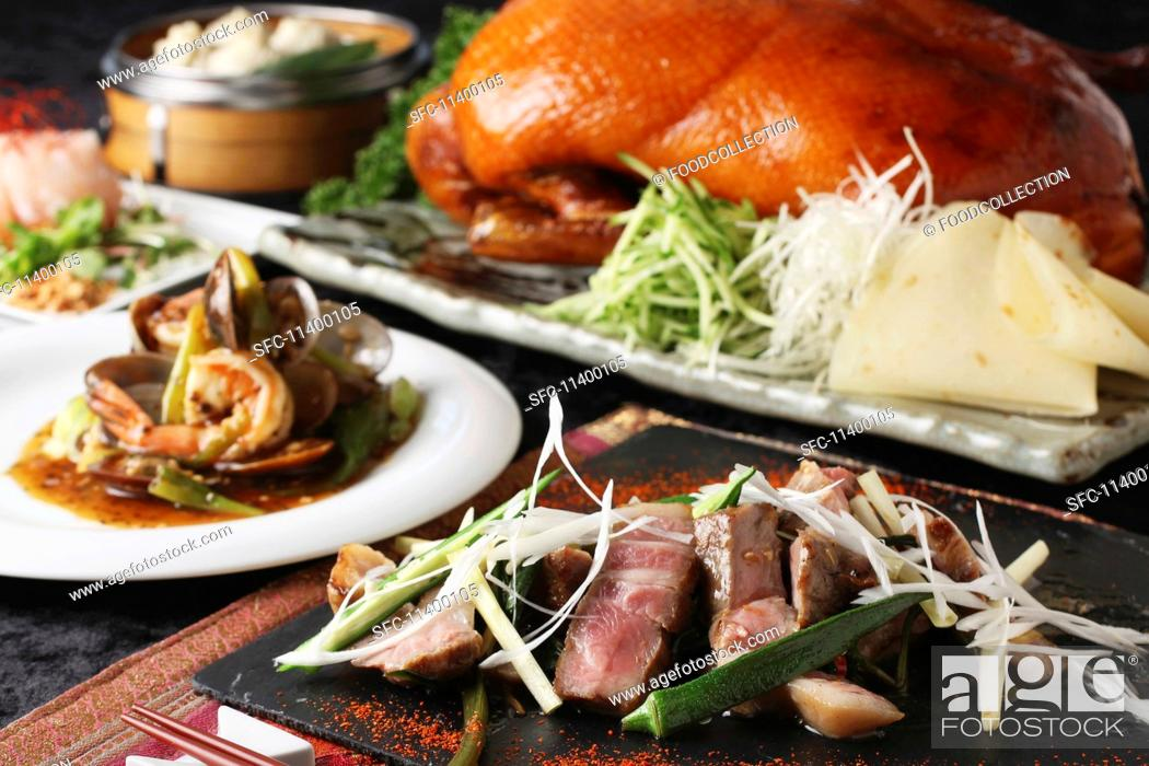 Stock Photo: A Chinese buffet featuring grilled beef, Peking duck and prawns with vegetables.