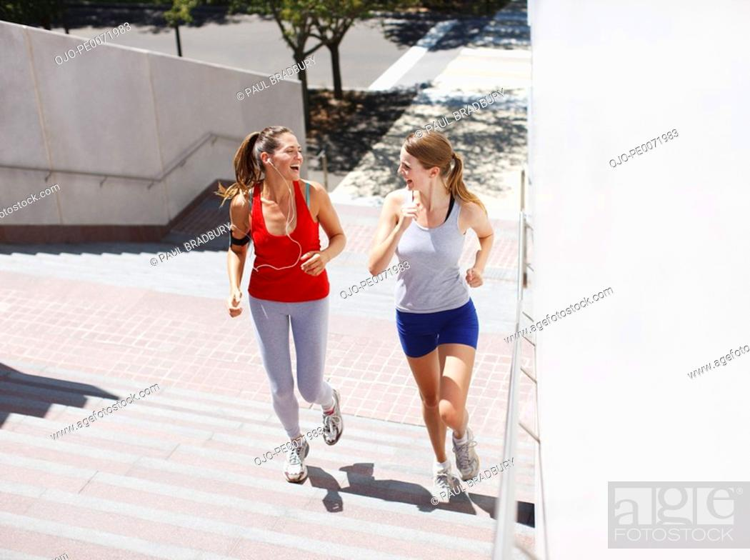 Stock Photo: Friends running up urban staircase.