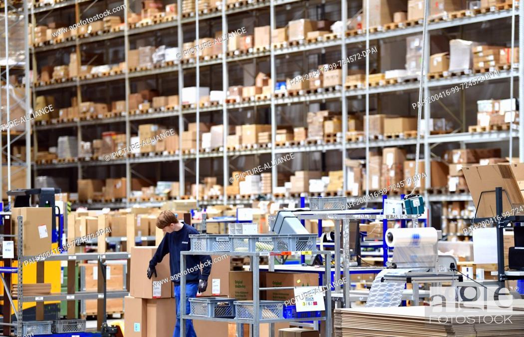 Stock Photo: 16 April 2020, Brandenburg, Großbeeren: A worker checks the goods at the logistics service provider Rhenus Warehousing Solutions SE & Co.