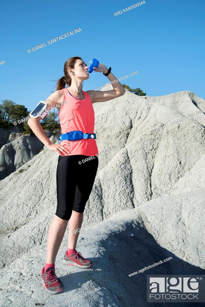 Stock Photo: Woman in sportswear drinking water after running in mountains, Gurb, Barcelona, Catalonia, Spain.