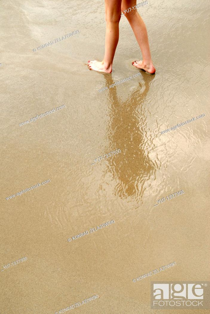 Stock Photo: Woman walking on a beach, Ionian Sea seashore near Sinarades town on greek island of Corfu.