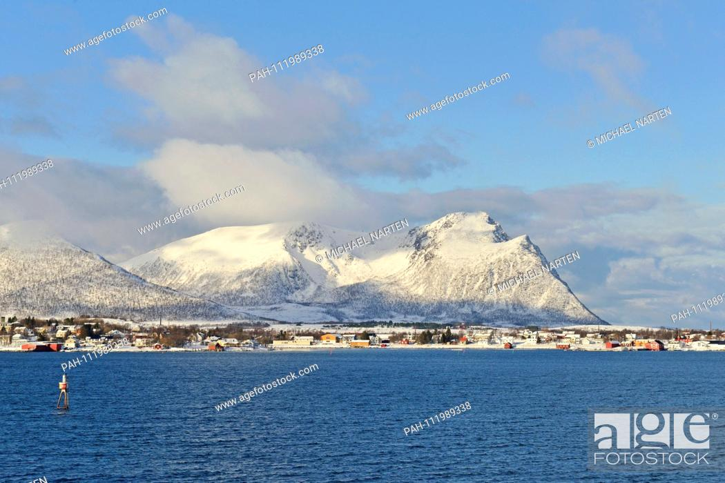 Stock Photo: Snowcapped mountains on the Vesterålen Island Andøya with buildings from the small village Risøyhamn at the waterside, 10 March 2017 | usage worldwide.