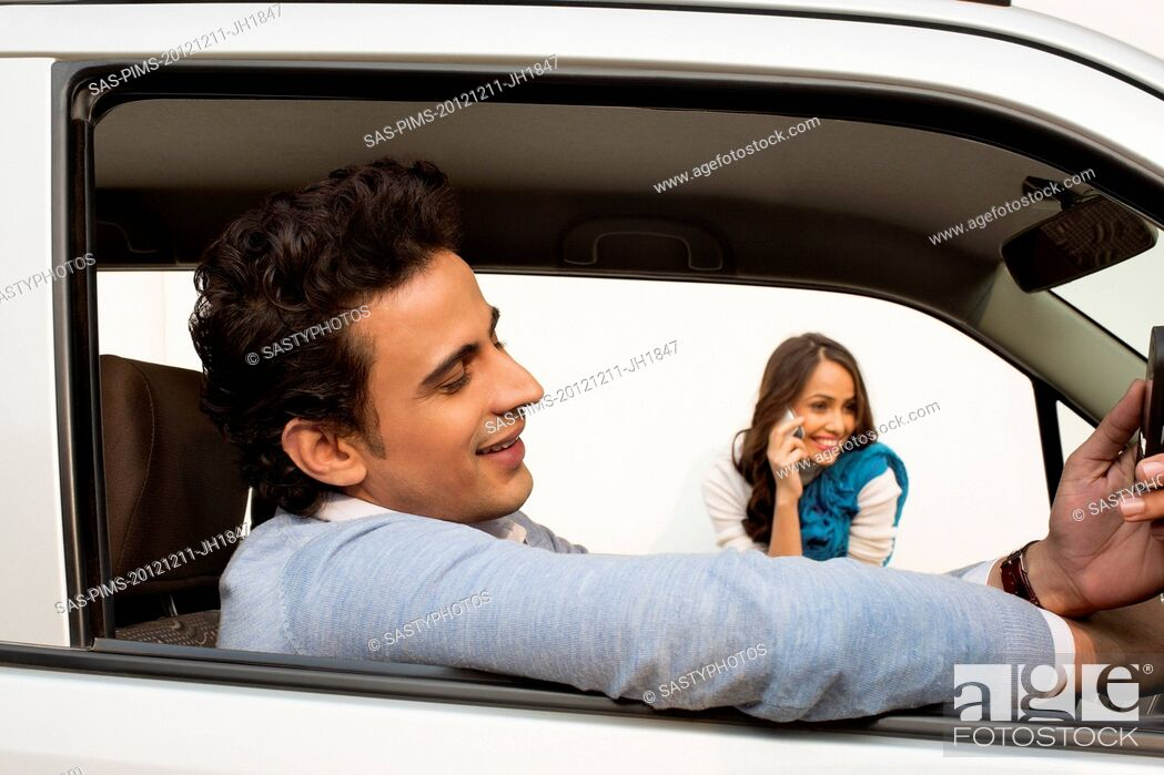 Stock Photo: Man sitting in a car with his girlfriend talking on mobile phone in background.