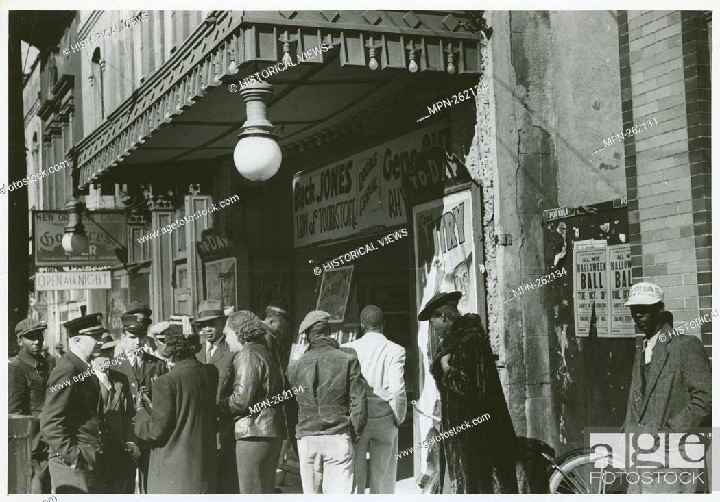 Stock Photo: Entrance to a movie house, Beale Street, Memphis, Tennessee, October 1939. Additional title: [African Americans and white police officers standing under an.