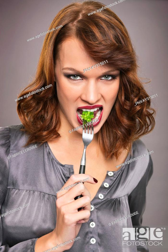 Stock Photo: Young woman eating broccoli.