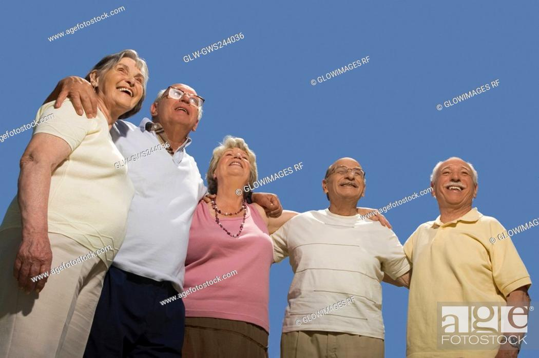 Stock Photo: Low angle view of senior people standing together with arm around.