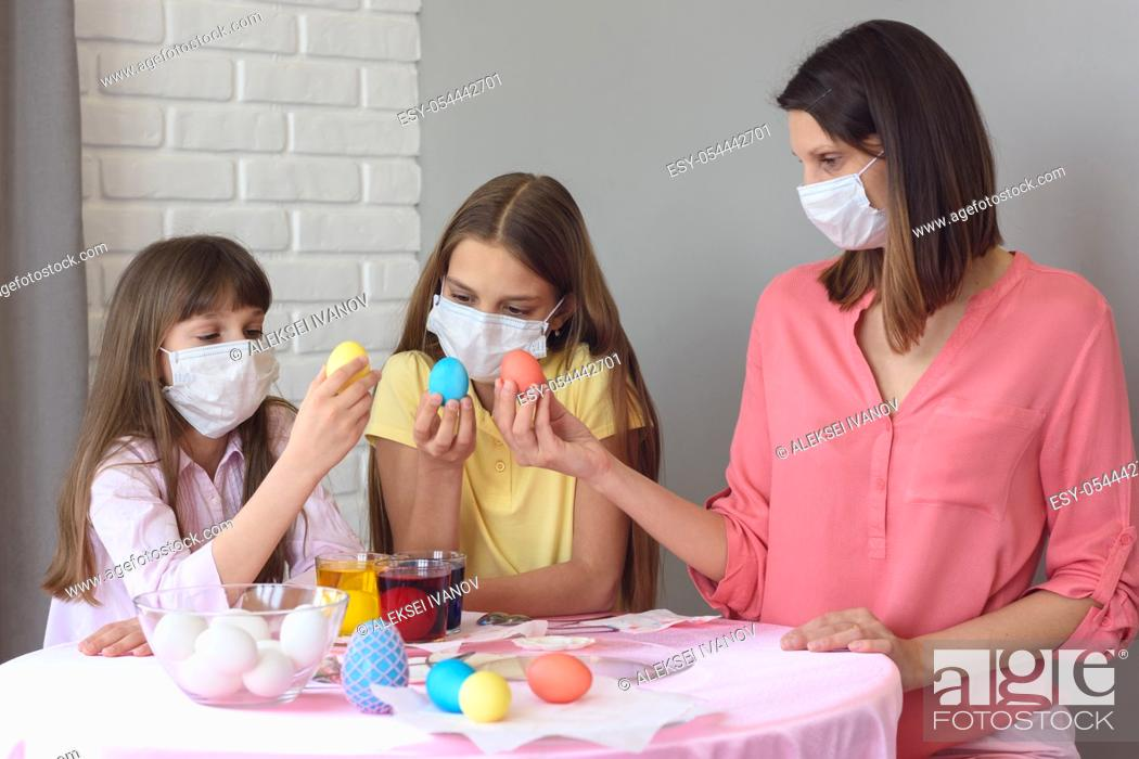 Stock Photo: Mom and two quarantined daughters painted eggs for Easter.