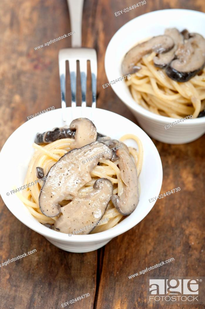 Stock Photo: Italian spaghetti pasta and fresh wild mushrooms on rustic wood table.