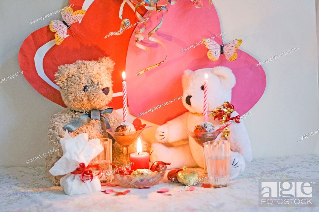 Stock Photo: RagTag Teddy Bear has a present for White Teddy Bear  Curly-haired brown teddy bear with a blue ribbon sits with a white teddy bear with gold and red ribbon.