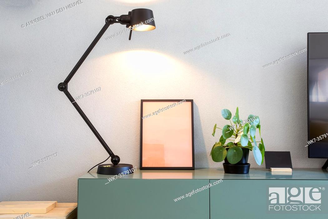 Stock Photo: Stylish modern interior, empty picture frame with black lamp and green Chinese Money plant, retro pancake plant on green table scandinavian design close-up.
