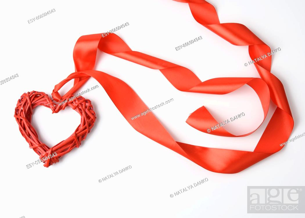 Stock Photo: red braided heart and twisted silk ribbon on white background, top view.