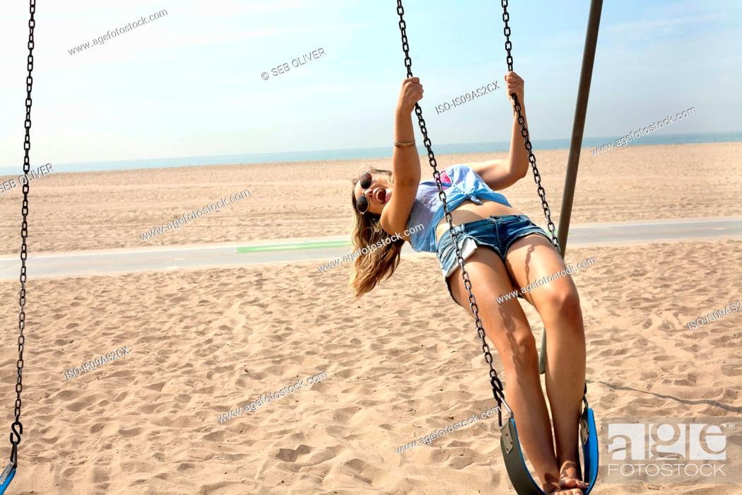 Imagen: Young woman on beach, swinging on playground swing.