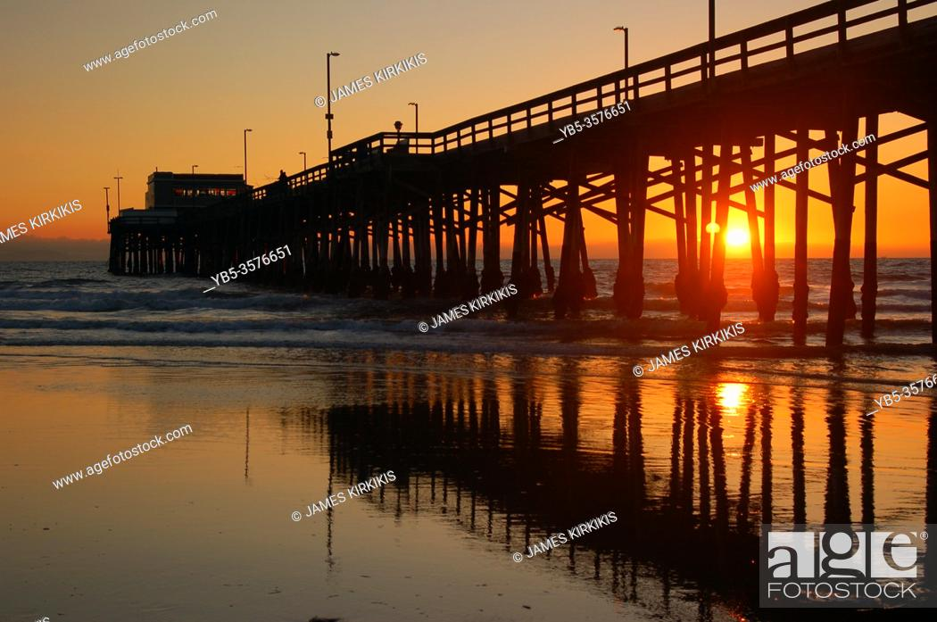 Stock Photo: The sun sets behind the Newport Beach Pier in Ocean County, California.