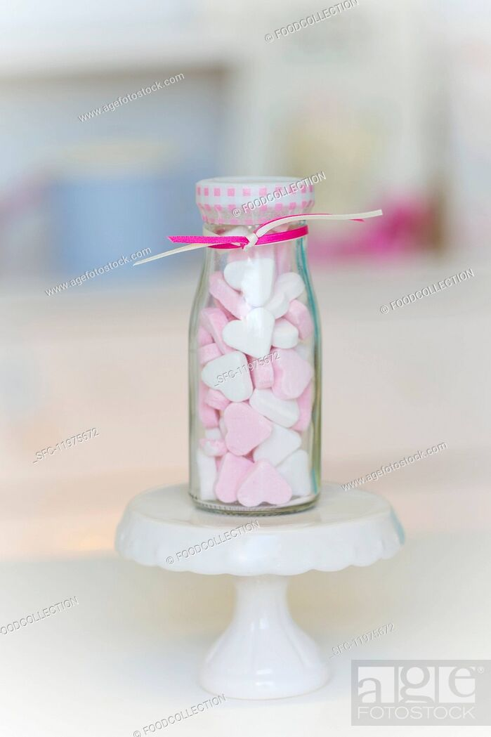 Imagen: Pink and white peppermint hearts in a small glass bottle.