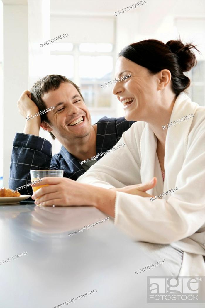 Stock Photo: Mid adult couple laughing at breakfast table.