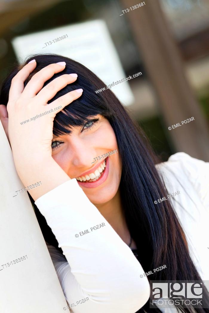 Stock Photo: Laughing and holding head young woman.