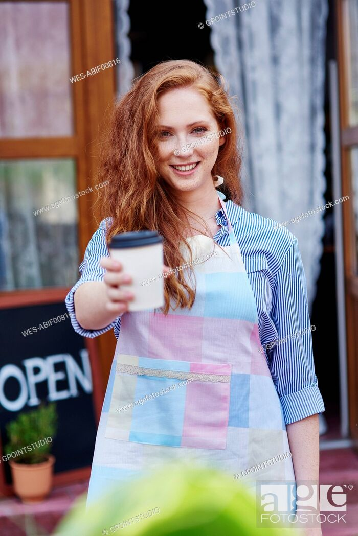 Stock Photo: Portrait of smiling waitress offering a coffee.