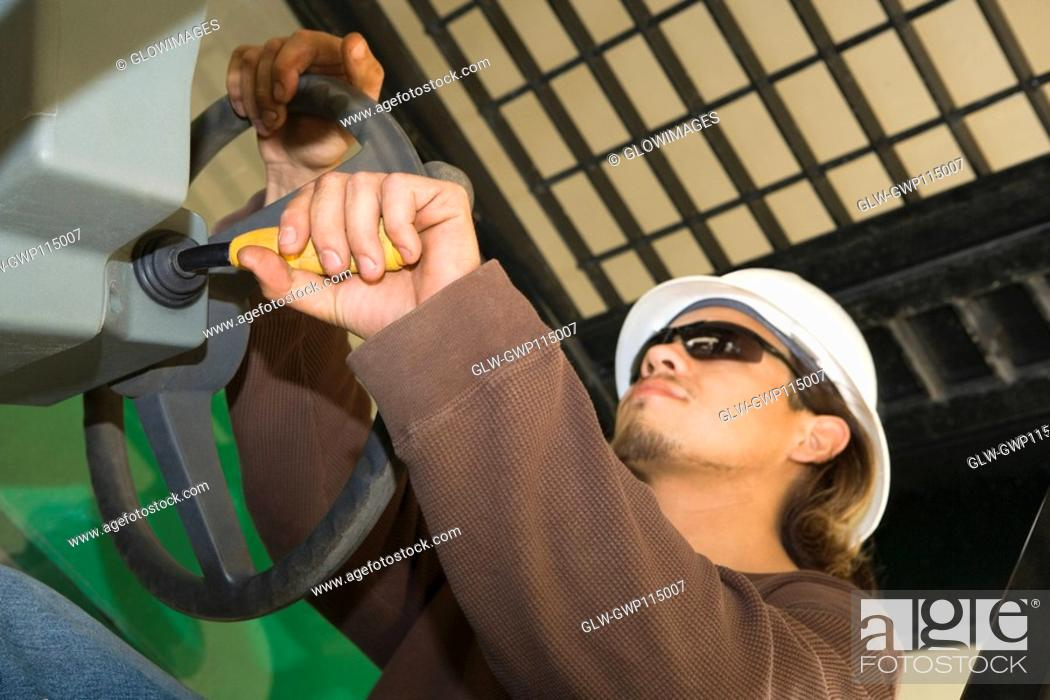 Stock Photo: Close-up of a male construction worker holding a steering wheel.