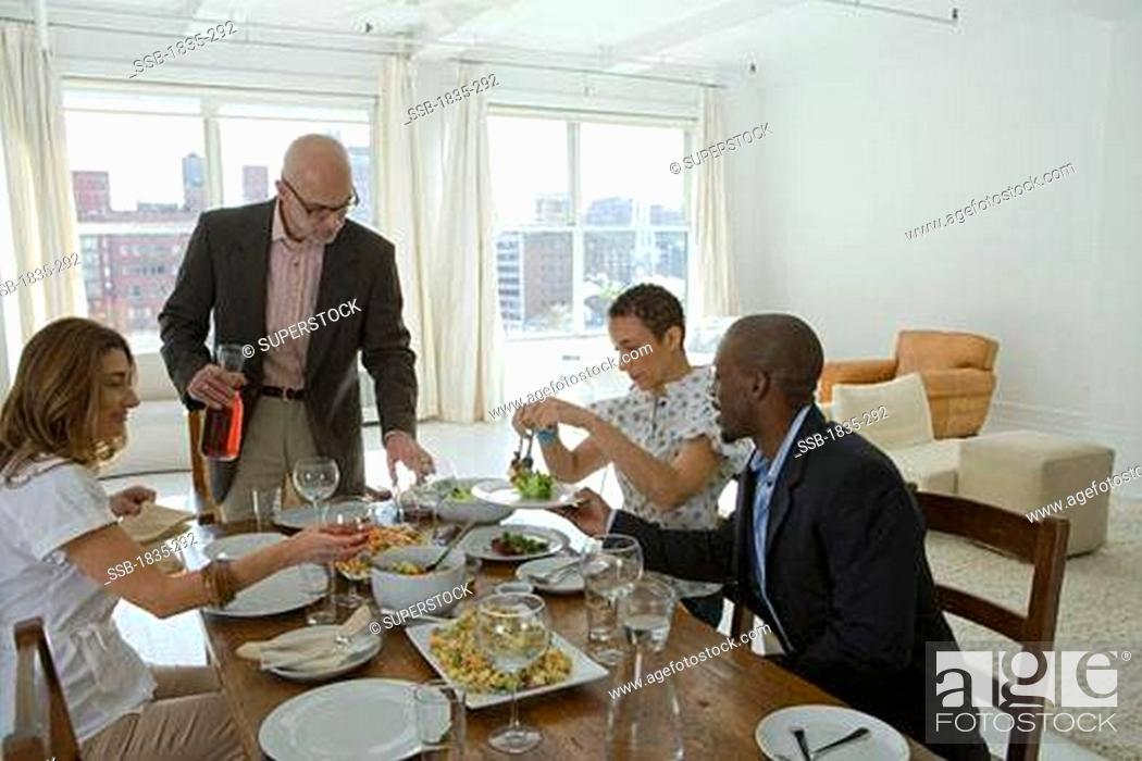 Stock Photo  Two men and two women at a dining table. 525c4de48