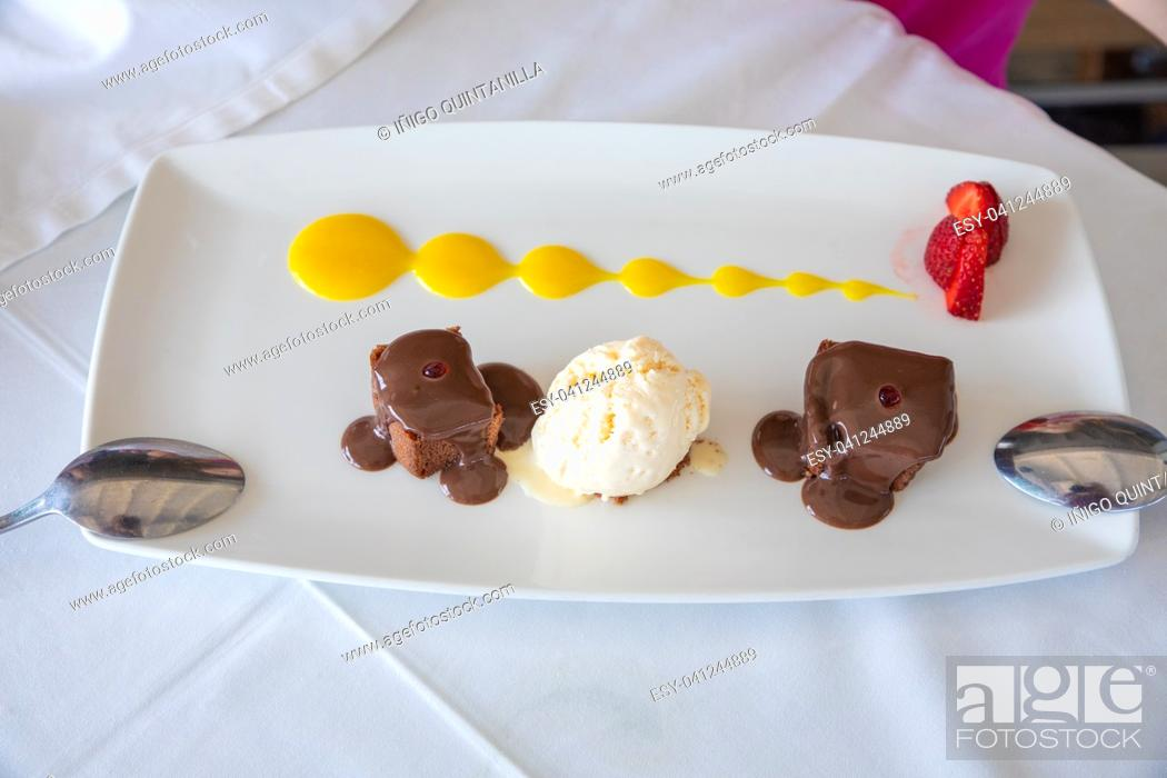 Imagen: tray with delicious sweet dessert: black chocolate, vanilla ice cream, strawberries and mango sauce, with two spoons in restaurant.