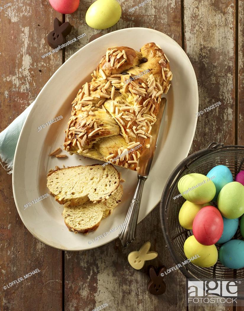 Stock Photo: A bread plait with flaked almonds and coloured Easter eggs in a wire basket.