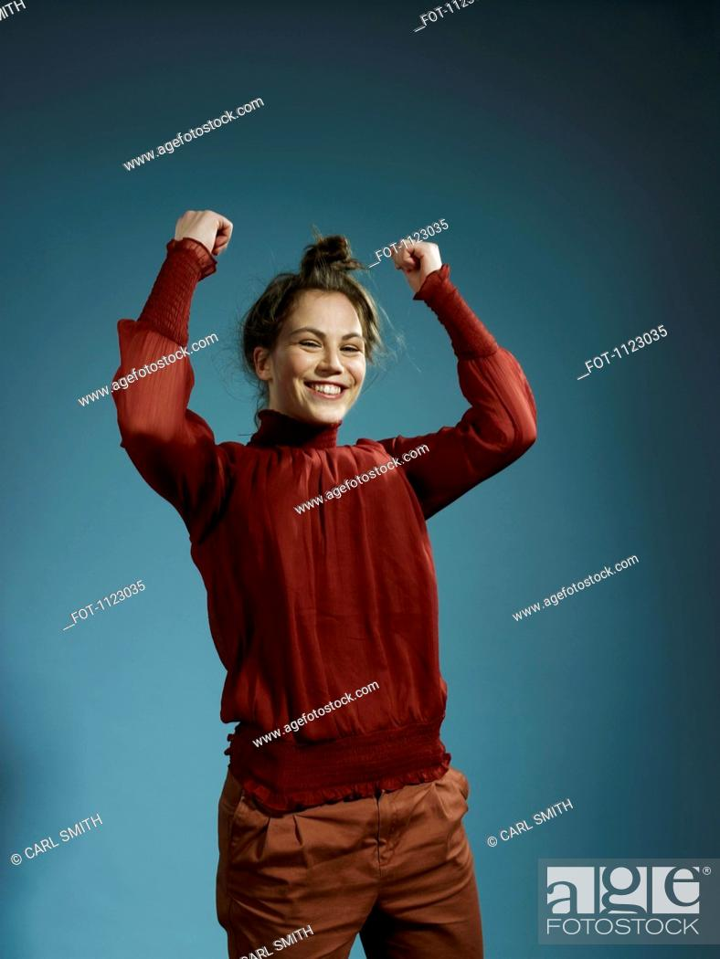 Stock Photo: A young woman with her arms raised in celebration.