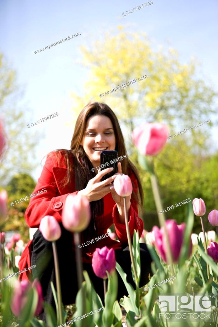 Stock Photo: A young woman photographing flowers with her phone.