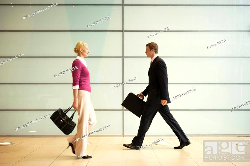 Stock Photo: Businesspeople Walking in Office Hallway side view.
