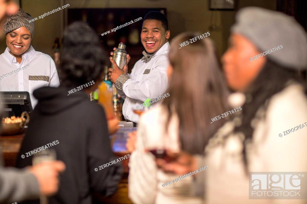 Stock Photo: Happy bartender making drinks in a bar.