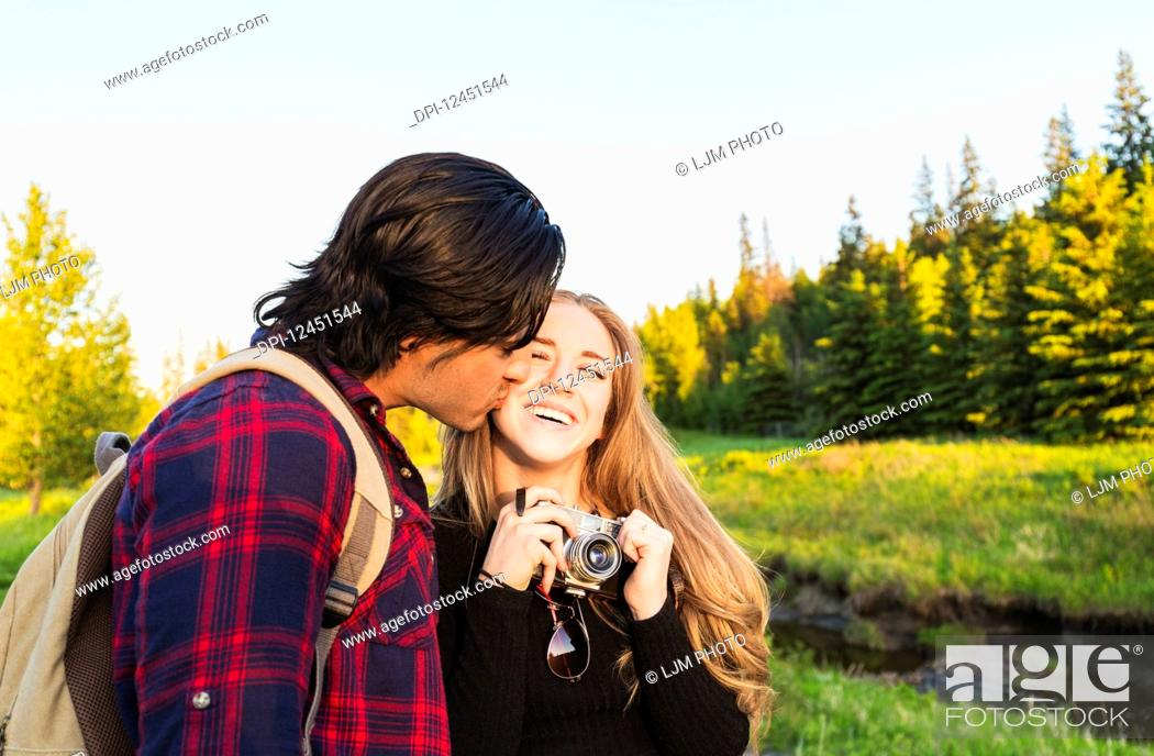 Photo de stock: Young couple walking together in a city park, the young woman holding a camera and the young man kissing her cheek; Edmonton, Alberta, Canada.