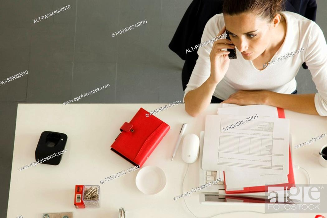 Stock Photo: Businesswoman at desk making phone call.