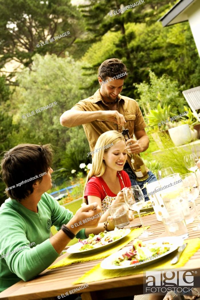 Stock Photo: 2 young men and a woman sitting at garden table, man opening wine bottle.