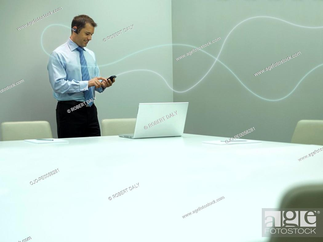 Stock Photo: Businessman standing with mobile phone with bright line is attaching the phone to earpiece.