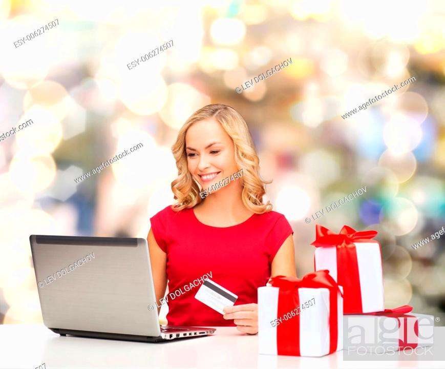 Stock Photo: christmas, holidays, technology and shopping concept - smiling woman in red blank shirt with gift boxes, credit card and laptop computer over lights background.
