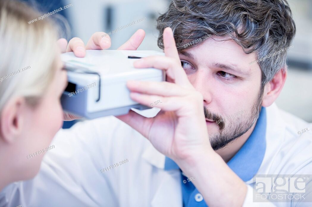 Stock Photo: Optometrist performing eye test of young woman.