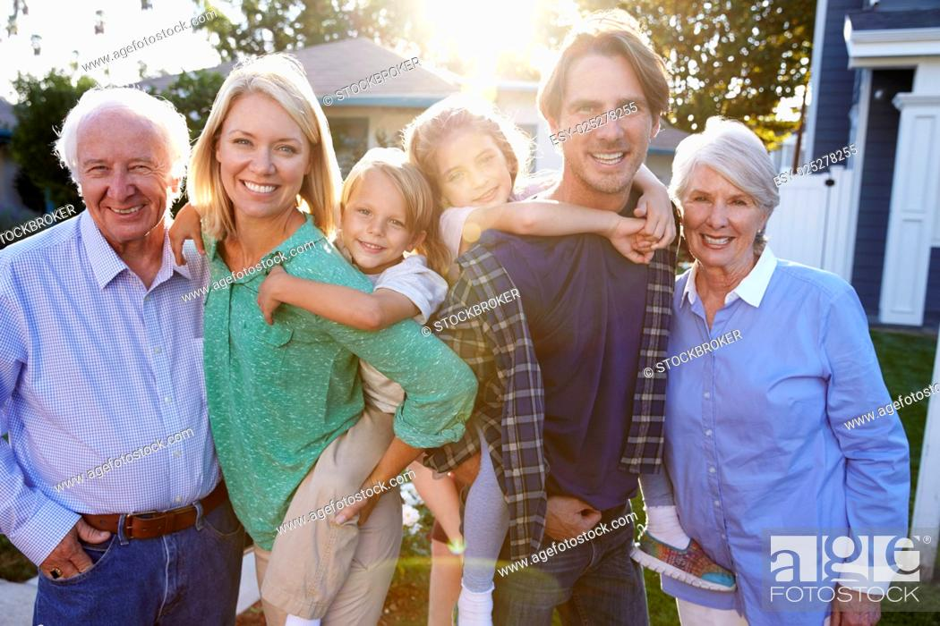 Stock Photo: Portrait Of Family With Grandparents Standing Outside House.