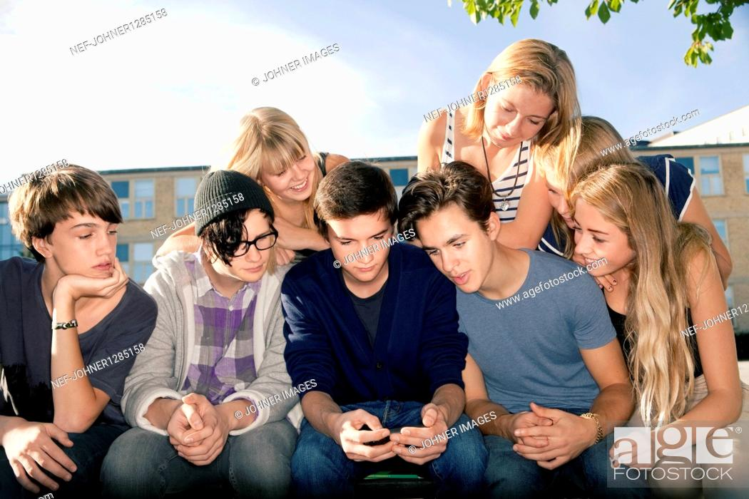 Stock Photo: Group of teenagers looking at mobile phone.