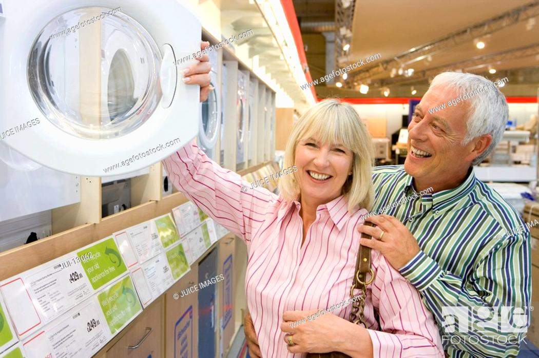 Stock Photo: Mature couple looking at washing machine in shop, smiling, portrait of woman.