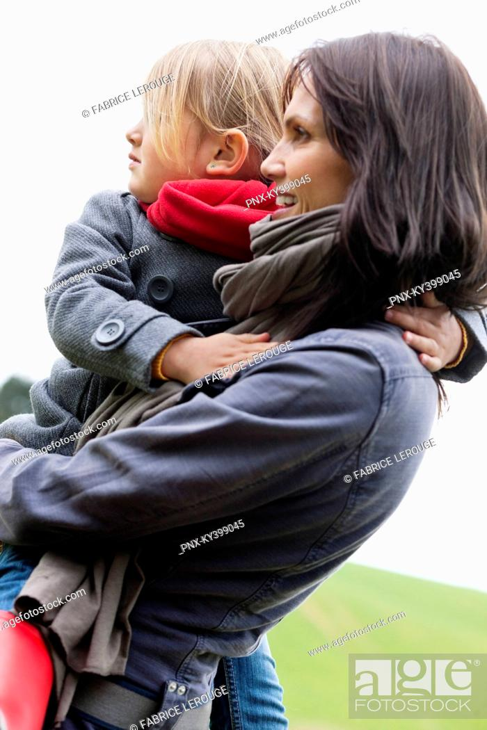 Stock Photo: Woman carrying her daughter.