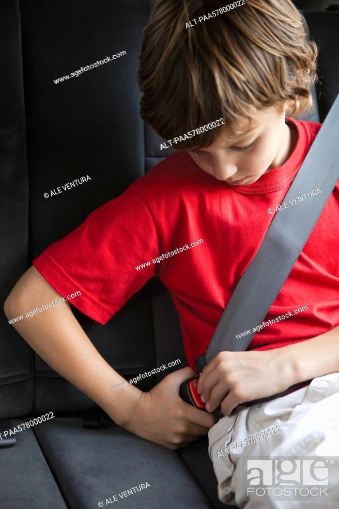Stock Photo: Boy fastening car seat belt.