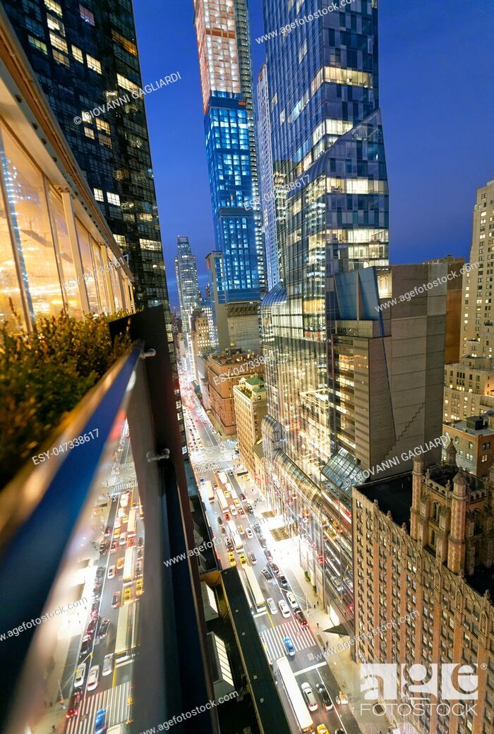 Stock Photo: Amazing skyscrapers in Midtown Manhattan, aerial view from rooftop with traffic reflections on the buildings at night.