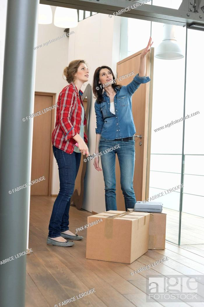 Stock Photo: Two female friends talking in their new house.