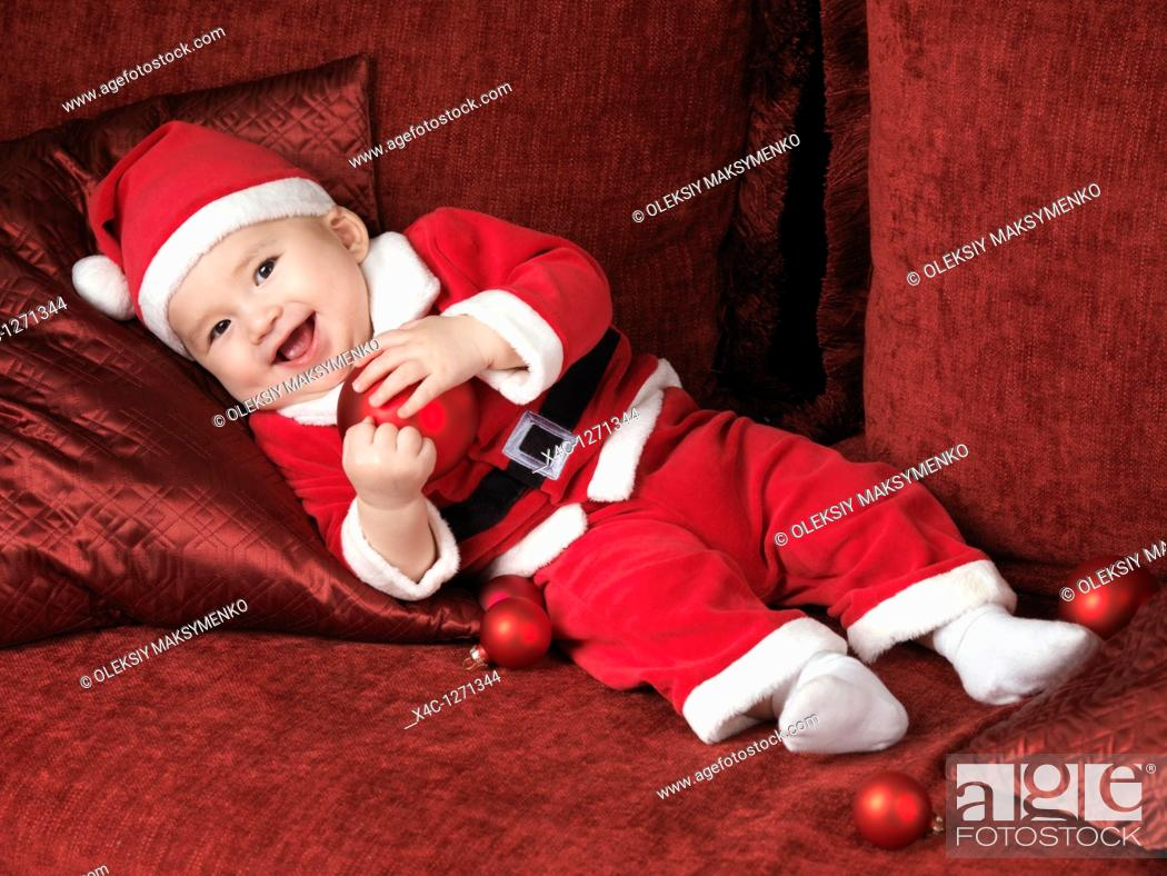 Stock Photo: Happy smiling six month old baby boy in Santa Christmas costume lying on a sofa with a red bauble in his hands.