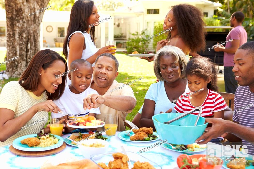 Stock Photo: Multi Generation Family Enjoying Meal In Garden Together.