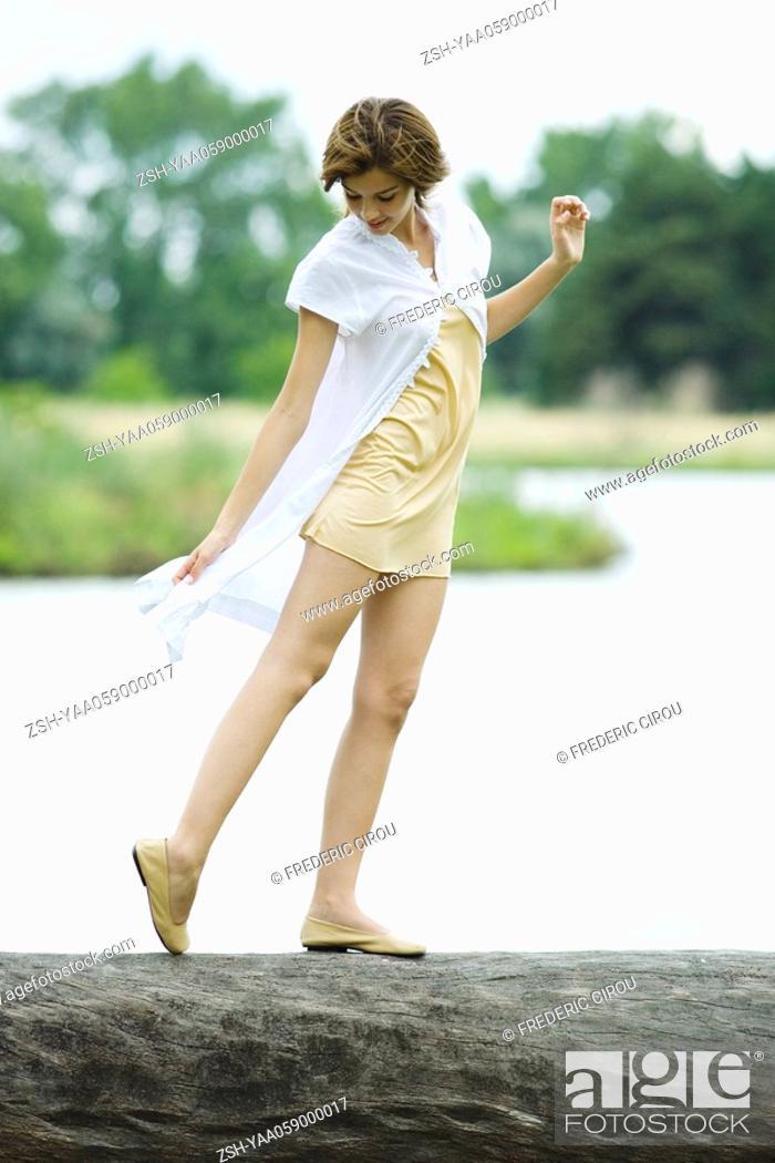 Stock Photo: Young woman walking along log, looking down at foot, full length.