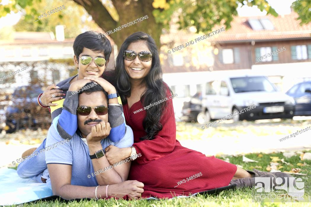 Imagen: Indian family relaxing on the grass. Tegernsee, Bavaria, Germany.