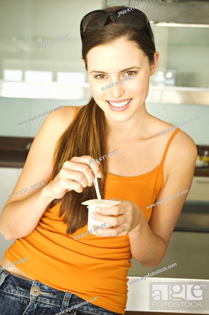 Stock Photo: Young smiling woman eating yogurt.